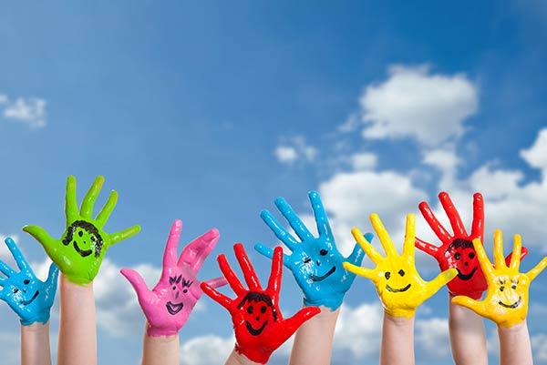 Bunt angemalte Kinderhände mit Gesichter