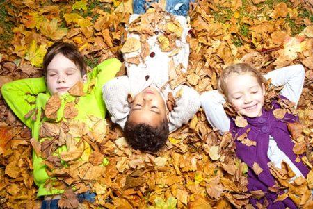 Kinder liegen entspannt im Laub
