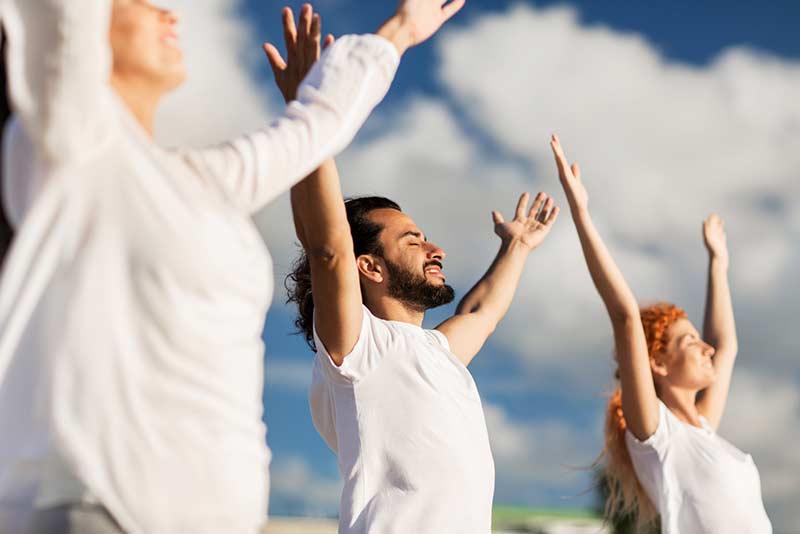Teilnehmer strecken Ihre Arme in den Himmel